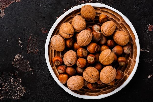 Смешайте полезные сырые фундук и грецкие орехи в керамической тарелке на коричневой бетонной поверхности.