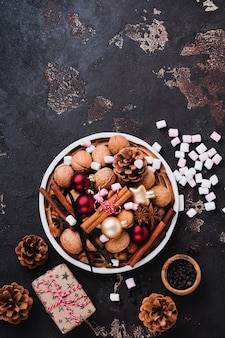Mix of healthy raw hazelnuts and walnuts, cinnamon sticks, anise, vanilla, chocolate and christmas toys in ceramic plate on brown concrete surface
