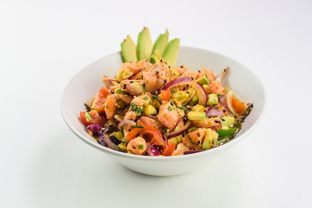 Mix japanese salad with salmon, tomato, avocado and onion.