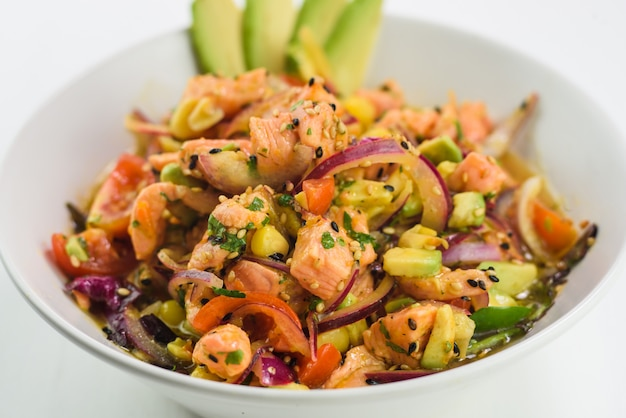 Mix japanese salad with salmon, tomato, avocado and onion