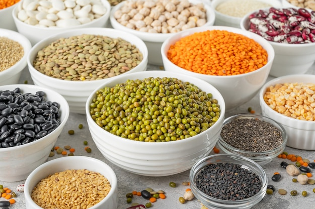 Mix of legumes, chickpeas, lentils, beans, peas, quinoa, sesame, chia and flax seeds in white bowls