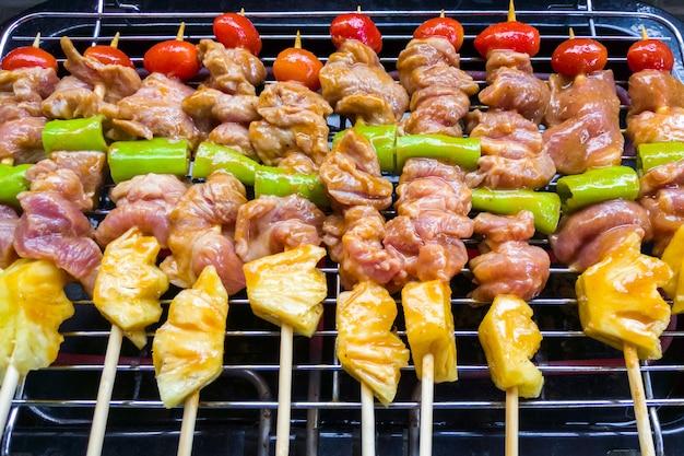 저녁 파티를 위해 그릴 스토브에서 구운 고기와 야채 바베큐를 섞어 구운 과정 사이에 바베큐 소스와 육즙이 풍부합니다.