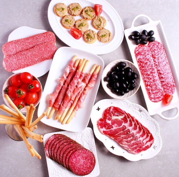 Mix of meat products and  appetizers served on table, top view