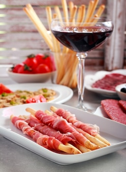 Mix of meat products and  appetizers served on table