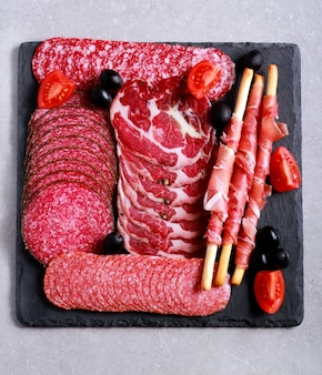 Mix of meat products on black board, top view