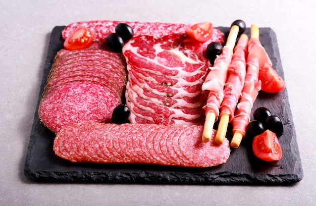 Mix of meat products on black board
