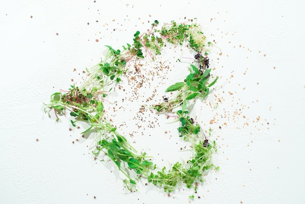 Mix of microgreens in the shape of a heart on a white background.