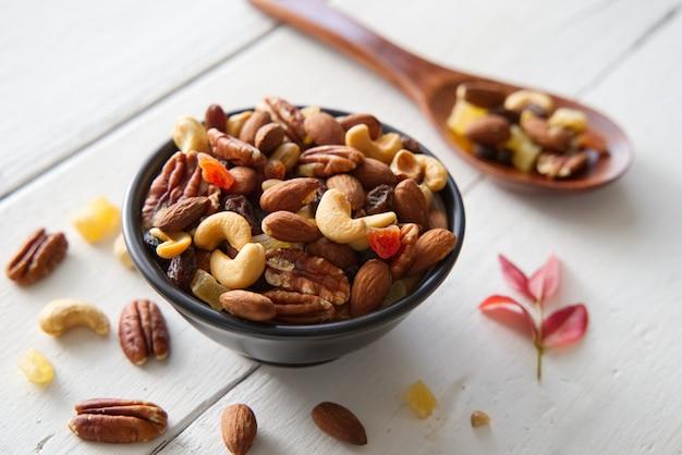 견과류와 말린 과일 배경과 벽지를 섞는다. 그릇에 믹스 너트와 말린 과일의 평면도에서 볼 수 있습니다.
