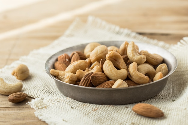 Mix nuts and dried fruits background and wallpaper. seen in top view of mix nuts and dried fruits in the bowl and wood spoon decorated with some nuts and green leaf on white wood in background.