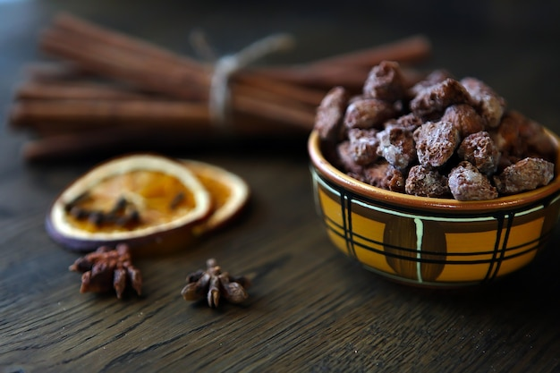 Mix nuts dry fruits and chocolate at ceramic bowl on the wooden table rustic style tasty and delicio...