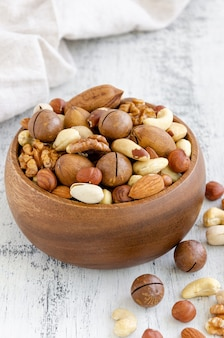 Mix of nuts in a wooden bowl. healthy food concept. .