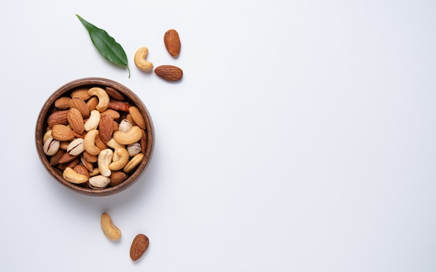 Mix of nuts on wooden bowl on light background
