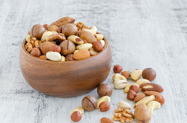 Mix of nuts in a wooden bowl on a light wooden background. healthy food concept. horizontal, selective focus.