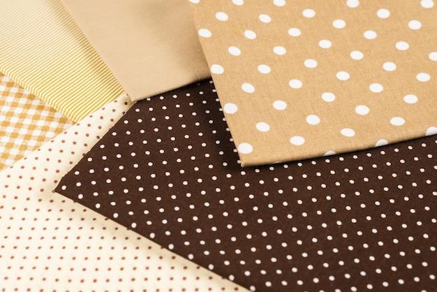 Смесь бежевой, белой и коричневой хлопчатобумажной ткани.