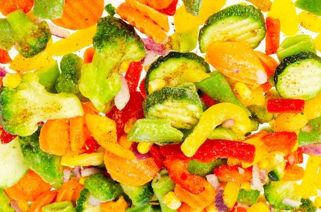鮮やかに刻んだ冷凍野菜を混ぜます。健康的な食事。スタジオ写真