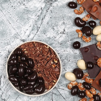 Смесь битых плиток шоколада, шоколадной стружки, сладкого кешью и орехов в шоколаде на сером каменном фоне. вид сверху с копией пространства