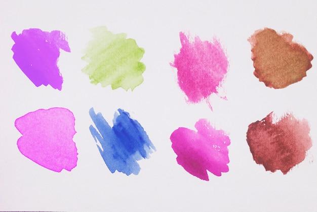 白い紙の茶色、緑色、青色、紫色、ピンク色の塗料の混合