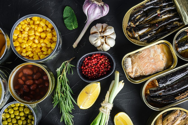 Смесь консервов в консервных банках со свежими органическими био ингредиентами, помидорами, травами, лимоном на черной доске.