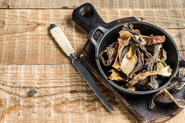 Смесь нарезанных лесных сушеных грибов на сковороде