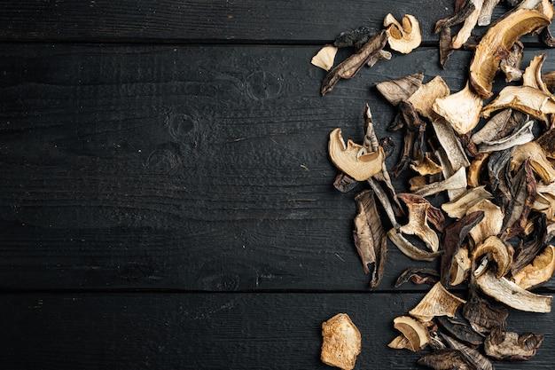 잘게 잘린 야생 말린 버섯 세트를 검은색 나무 테이블 배경에 혼합하고, 위쪽 뷰 플랫 레이, 텍스트 카피스페이스를 위한 공간