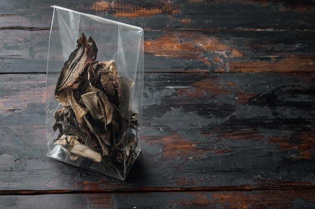 오래 된 어두운 나무 테이블 배경에 잘게 잘린 야생 말린 버섯 세트, 플라스틱 팩, 텍스트 복사 공간을 위한 공간