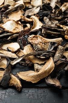 古い暗い木製のテーブルの上に、刻んだ野生の乾燥キノコのミックスセット