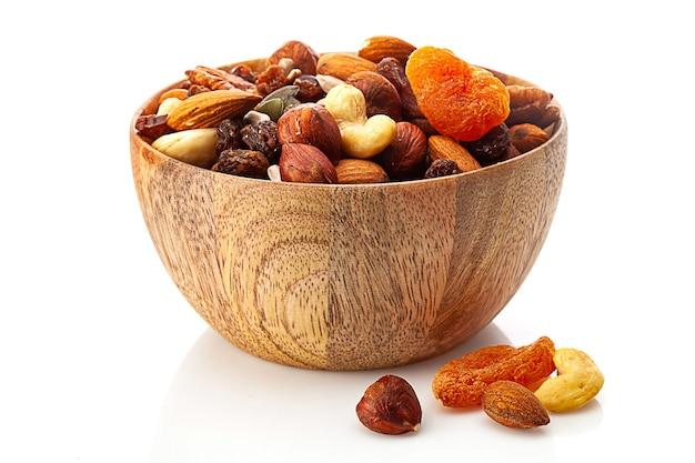 Смесь различных орехов и сухофруктов в деревянной миске, изолированные на белом фоне