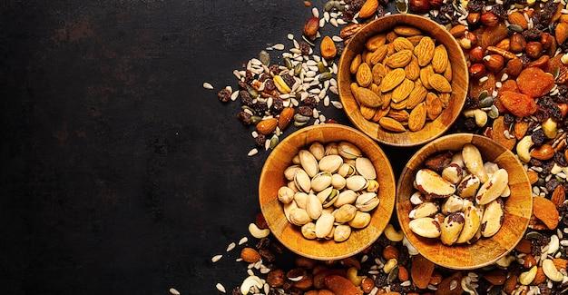 Смесь разных орехов и сухофруктов в деревянной миске, стоящей на деревенском