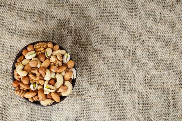 Смешайте различные орехи в деревянной чашке против ткани из мешковины. гайки как структура и предпосылка, макрос. вид сверху.
