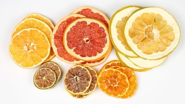 흰색 배경에 말린 감귤류 과일의 다른 조각을 섞습니다. 건강한 비타민 식품