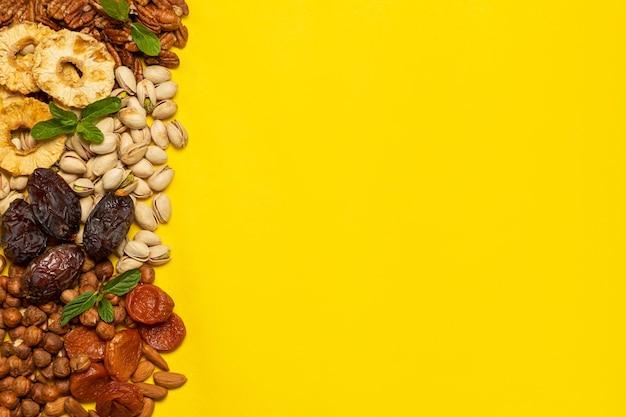 ドライフルーツと天日干しフルーツ、黄色の背景にコピースペースのあるナッツのミックス..tubishvatのユダヤ教の祝日のシンボル