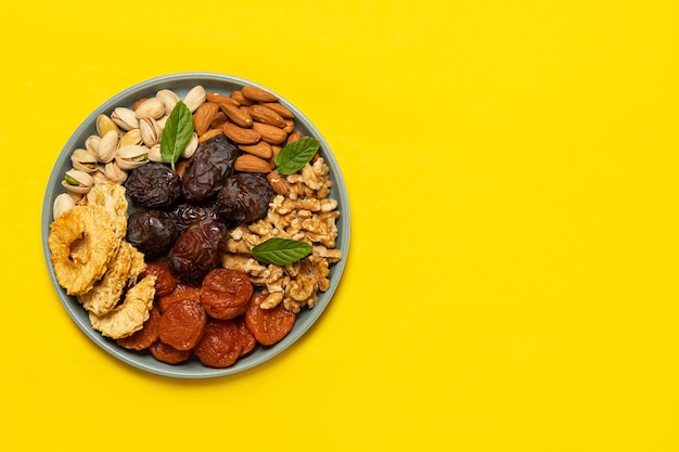 コピースペースのある黄色の背景のプレートにドライフルーツとナッツを混ぜます。上からの眺め。樹木の新年のユダヤ教の祝日のシンボル