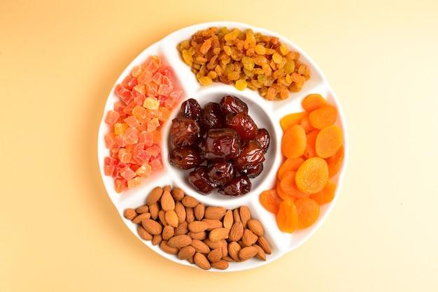 흰 접시에 말린 과일과 견과류를 섞으세요. 살구, 아몬드, 건포도, 날짜 과일. 베이지색 배경에. 텍스트 또는 디자인을 위한 공간입니다.