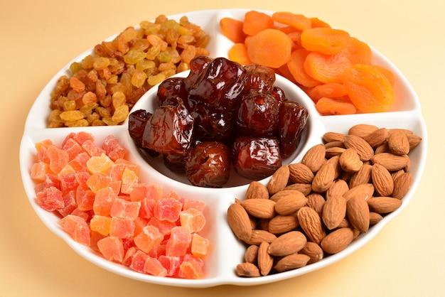 白い皿にドライフルーツとナッツを混ぜる。アプリコット、アーモンド、レーズン、ナツメヤシ。ベージュの壁に。テキストやデザインのためのスペース。