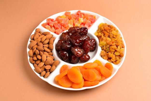 白い皿にドライフルーツとナッツを混ぜる。アプリコット、アーモンド、レーズン、ナツメヤシ。茶色の背景に。テキストやデザインのためのスペース。