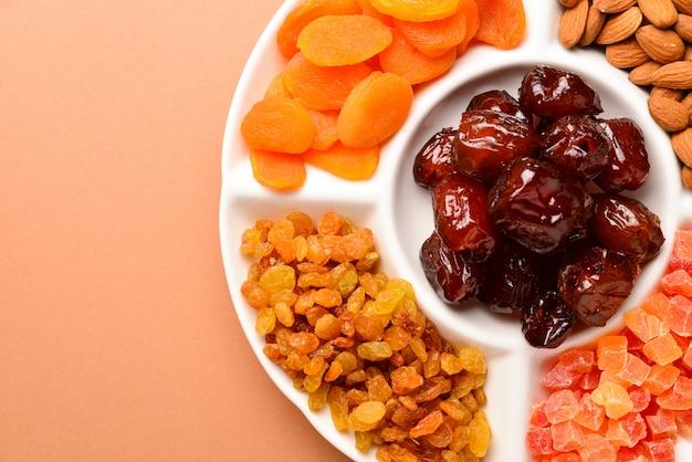 白い皿にドライフルーツとナッツのミックス。アプリコット、アーモンド、レーズン、フルーツの日付。茶色の背景に。テキストまたはデザインのためのスペース。