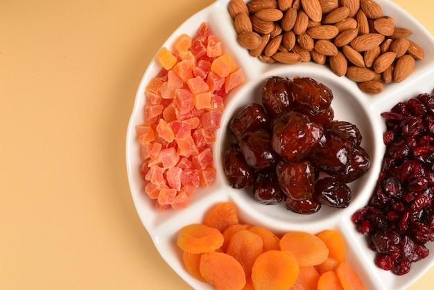 흰색 접시에 말린 과일과 견과류의 혼합. 살구, 아몬드, 건포도, 대추 과일. 갈색 배경. 텍스트 또는 디자인을위한 공간.