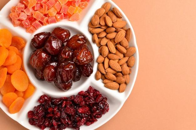 흰 접시에 말린 과일과 견과류를 섞으세요. 살구, 아몬드, 건포도, 날짜 과일. 갈색 배경에. 텍스트 또는 디자인을 위한 공간입니다.