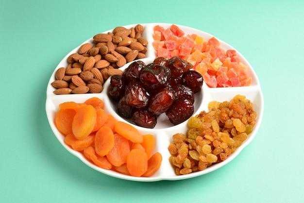 白い皿にドライフルーツとナッツを混ぜる。アプリコット、アーモンド、レーズン、ナツメヤシ。緑の背景に。テキストやデザインのためのスペース。