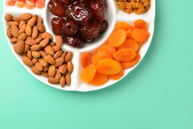 흰 접시에 말린 과일과 견과류를 섞으세요. 살구, 아몬드, 건포도, 날짜 과일. 녹색 배경에. 텍스트 또는 디자인을 위한 공간입니다.