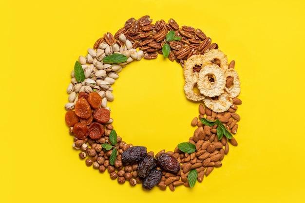 黄色の背景にドライフルーツとナッツのミックス。上面図。ユダヤの休日の樹木の新年のシンボル。感謝祭。フラットレイ、上面図、コピースペース