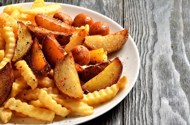 Микс картофеля фри, мексиканского картофеля и картофельных шариков на тарелке с копией пространства