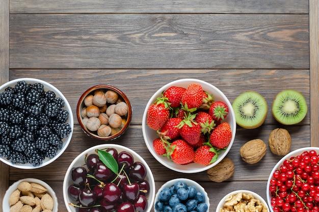 신선한 딸기, 견과류 및 과일의 혼합. 건강 식품에는 많은 비타민과 유용한 미량 원소가 포함되어 있습니다. 갈색 나무 배경. 공간을 복사하십시오.