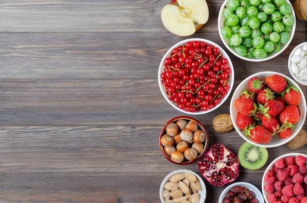 新鮮なベリー、ナッツ、フルーツのミックス。健康食品には、多くのビタミンと有用な微量元素が含まれています。茶色の木製の背景。スペースをコピーします。 Premium写真