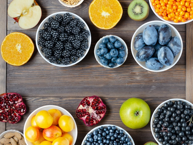 新鮮なベリー、ナッツ、フルーツのミックス。健康食品には、多くのビタミンと有用な微量元素が含まれています。茶色の木製の背景。スペースをコピーします。