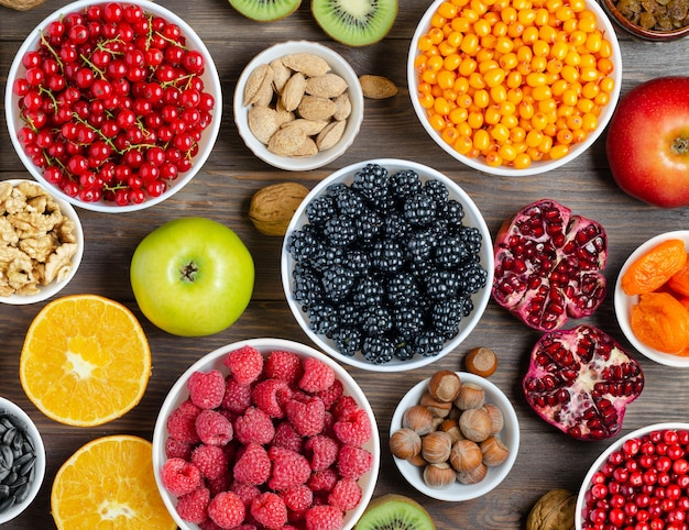 新鮮なベリー、ナッツ、フルーツのミックス。健康食品には、多くのビタミンと有用な微量元素が含まれています。茶色の木製の背景。