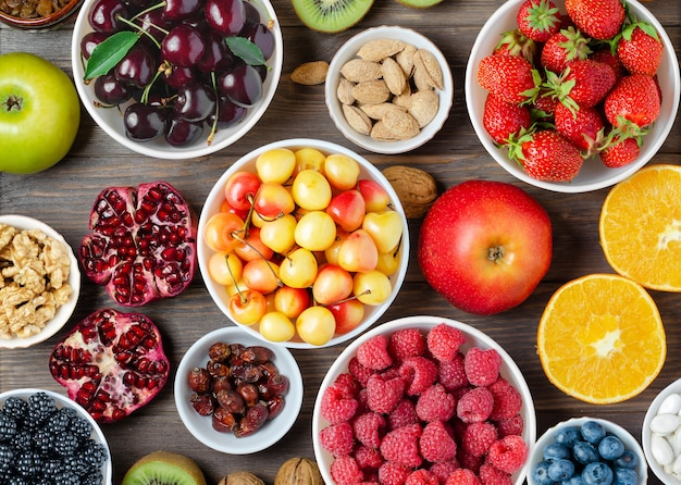 신선한 딸기, 견과류 및 과일의 혼합. 건강 식품에는 많은 비타민과 유용한 미량 원소가 포함되어 있습니다.