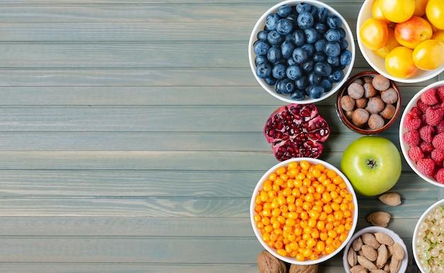 新鮮なベリーナッツとフルーツのミックス木製の背景コピースペース