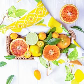 白い木製の背景のバスケットに新鮮な色の柑橘系の果物のミックス