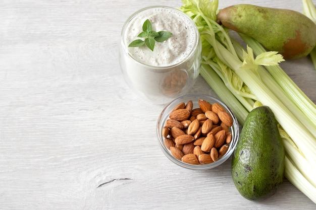 新鮮な緑の野菜のミックス:テキスト用のスペースのあるテーブルにアボカド、セロリ、アーモンド、洋ナシ、グリーンスムージー。